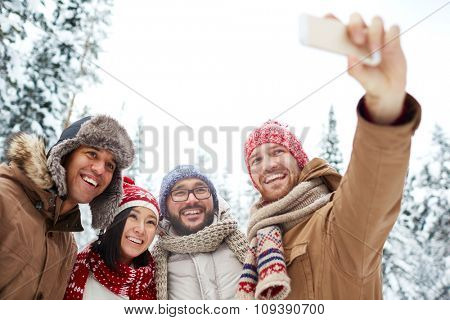 Young friends in winterwear making selfie in natural environment
