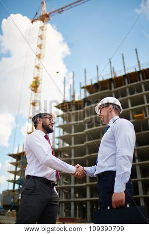 Young architects or builders handshaking after making agreement