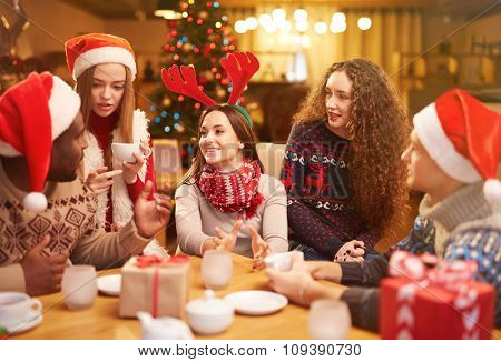 Happy friends having tea on Christmas eve