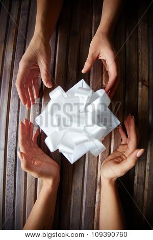 Female hands giving and taking Christmas present