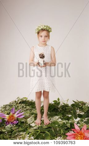 Portrait of the beautiful little girl of the child with a fine wreath on the head
