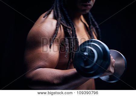 Young muscular man exercising with barbells