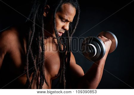 Topless young athlete with dreadlocks exercising with barbell
