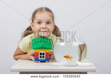 Four-year Girl Holding A Toy House And Sits In Front Of A Goldfish