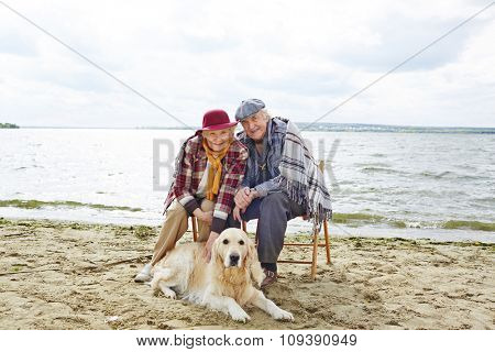 Two pensioners resting by seaside with their pet