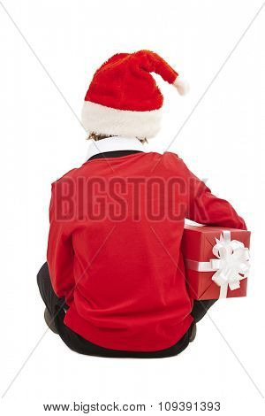 Rear view of boy in Santa cap holding gift-box
