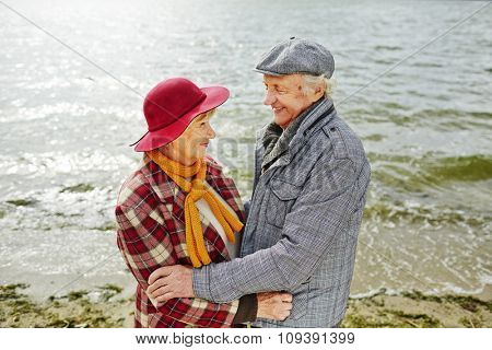 Amorous aged couple looking at one another standing by seaside