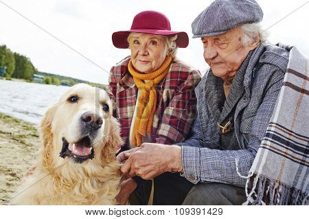 Retired couple and their pet enjoying weekend rest by seaside