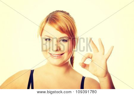 Portrait of happy overweight woman showing OK sign