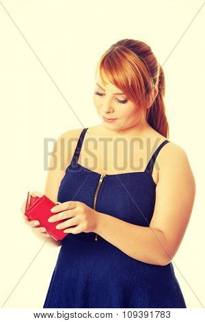 Overweight woman holding an empty wallet.