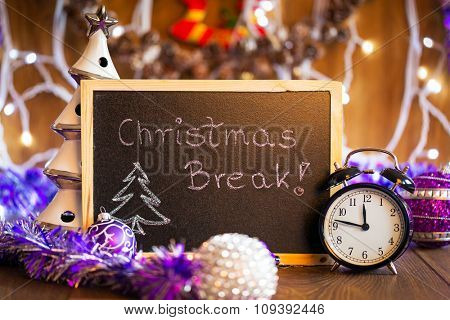Winter Break written on the black chalkboard with Christmas decorations and lights