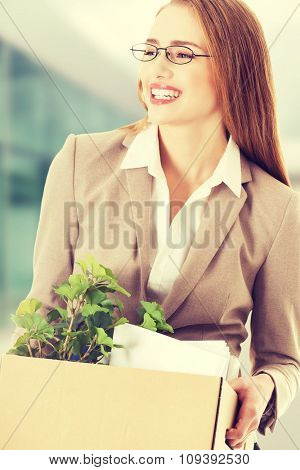 Beautiful business woman holding box with office items.