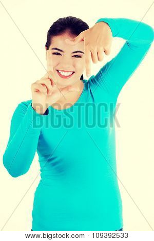 Happy young woman gesturing frame.