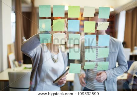 Employees reading working points and making notes on reminders in office