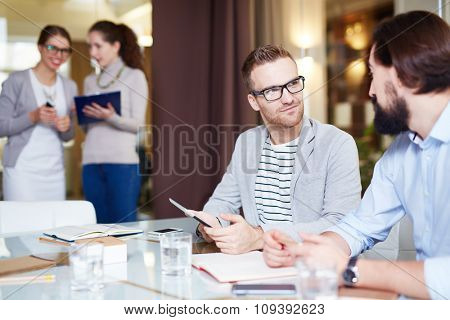 Modern manager with touchpad looking at colleague during conversation