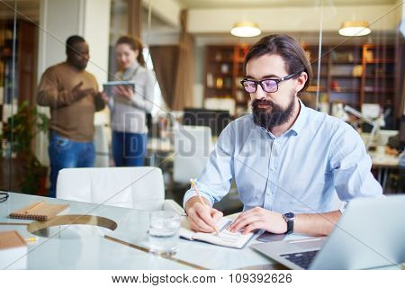 Caucasian male employee writing plan in office