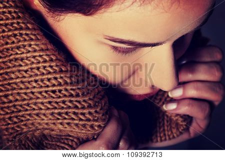 Portrait of a woman wrapped in warm scarf.