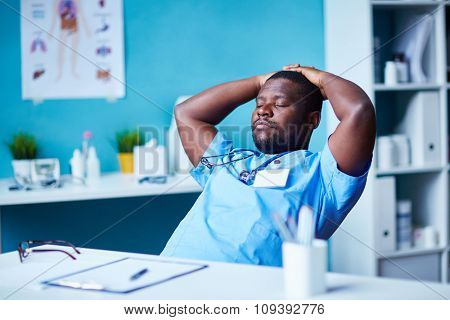 Young clinician with closed eyes relaxing at workplace during break