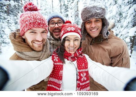 Multi-ethnic group of friends making selfie in park