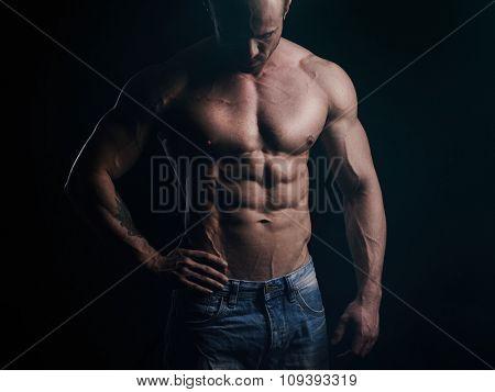 Shirtless athlete looking at his body