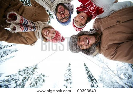 Joyful friends looking at camera in winter environment