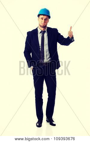 Happy smiling businessman in hard hat with thumbs up gesture.