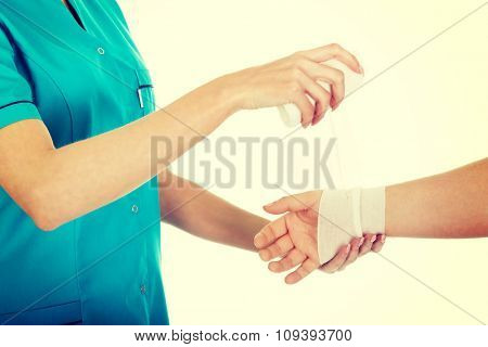 Caucasian woman doctor bandaging female hand