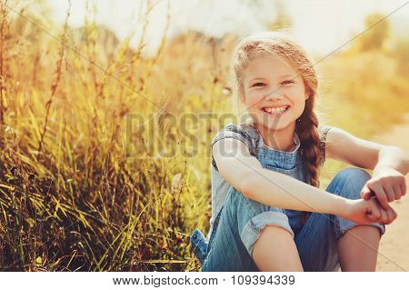 Happy Child Girl In Jeans Overall Playing On Sunny Field