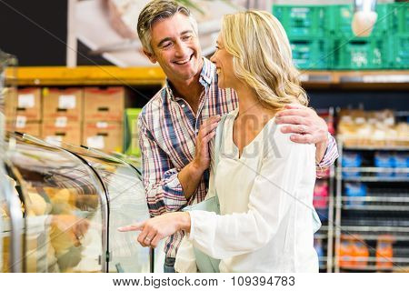 Happy couple buying food in supermarket
