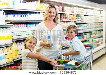 Portrait of beautiful mother with her children at the supermarket