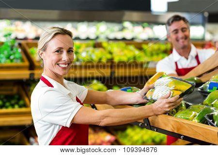 Smiling woman filling vegetables boxes at supermarket