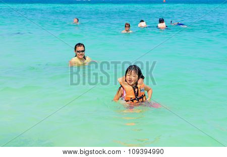 People Relaxing, Swimming, Having Fun On The Beach