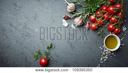 Cherry tomatoes, herbs, spices and olive oil on a stone background