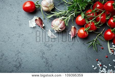 Cherry tomatoes, herbs and spices on  a stone background
