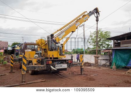 Technician With Machine For Drilling Holes In The Ground At Construction Site