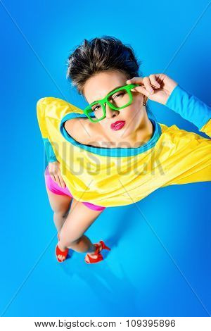 Glamorous fashion model posing in vivid colourful clothes and glasses. Bright fashion. Optics, eyewear. Studio shot.