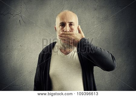 bearded senior man covering his mouth and looking at camera over grey wall