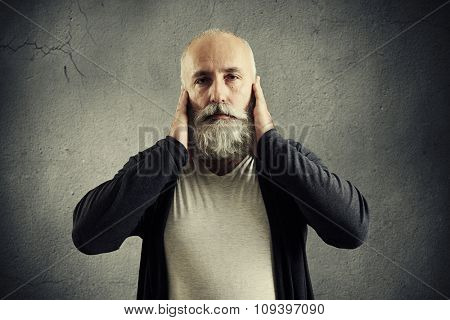 bearded senior man covering his ears and looking at camera over dark wall