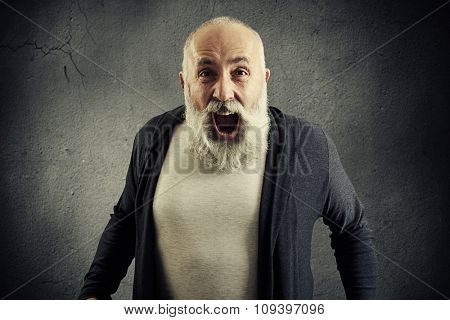 emotional screaming senior man with beard over dark wall