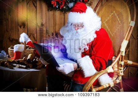 Modern Santa Claus at his wooden house surfing in the Internet with his laptop. Christmas.