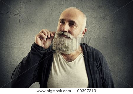 smiley senior man twisting his mustache and dreaming looking up over grey background