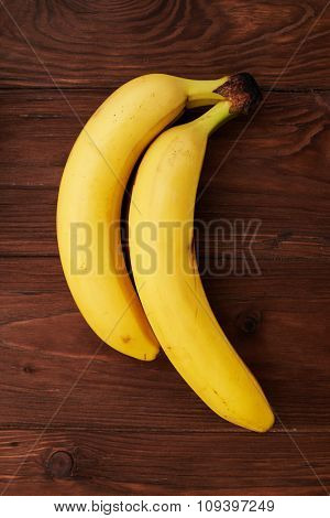 two yellow fresh bananas on brown wooden background