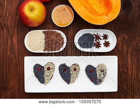 tasty raw cookies and healthy ingredients on wooden brown background