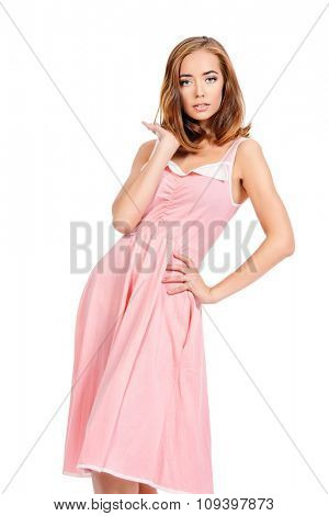Portrait of a beautiful young woman in pink summer dress. Isolated over white. Copy space.