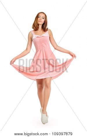 Beautiful young woman in a pink summer dress. Isolated over white.