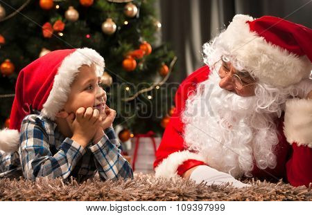 Santa Claus and a little boy in conversation in front of Christmas Tree