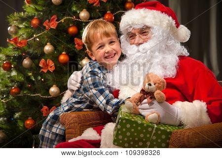 Santa Claus and a little boy. Boy embraces Santa Claus
