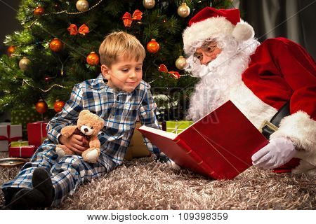 Santa Claus and a little boy reading together a book in front of Christmas Tree