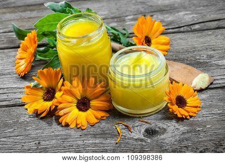 Homemade calendula ointment on wooden table