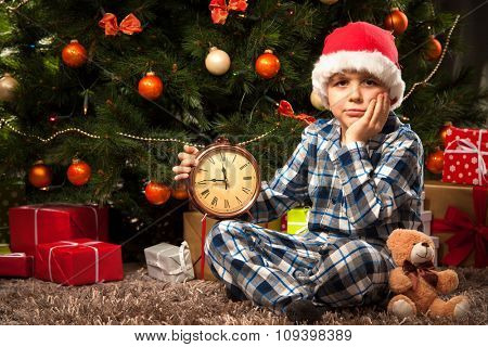 Little boy in pajama with the alarm clock waiting impatiently for Santa